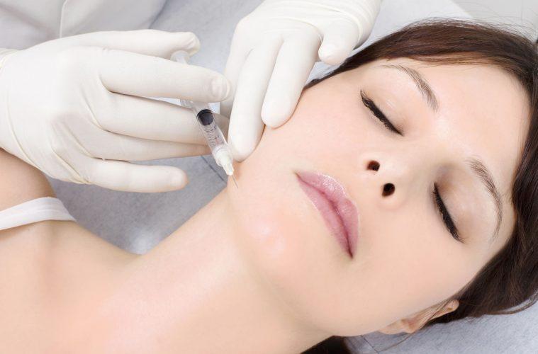 Девушке делают инъекцию в лицо