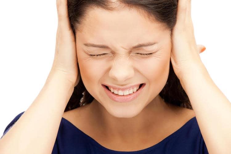 девушка держится за уши и закрыла глаза