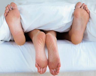 две пары ног в постели