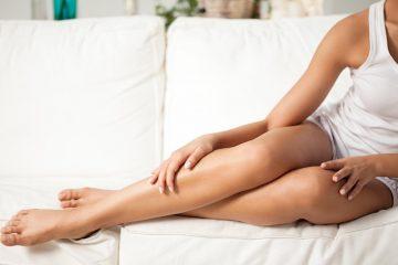 красивые ноги без варикоза лежат на диване