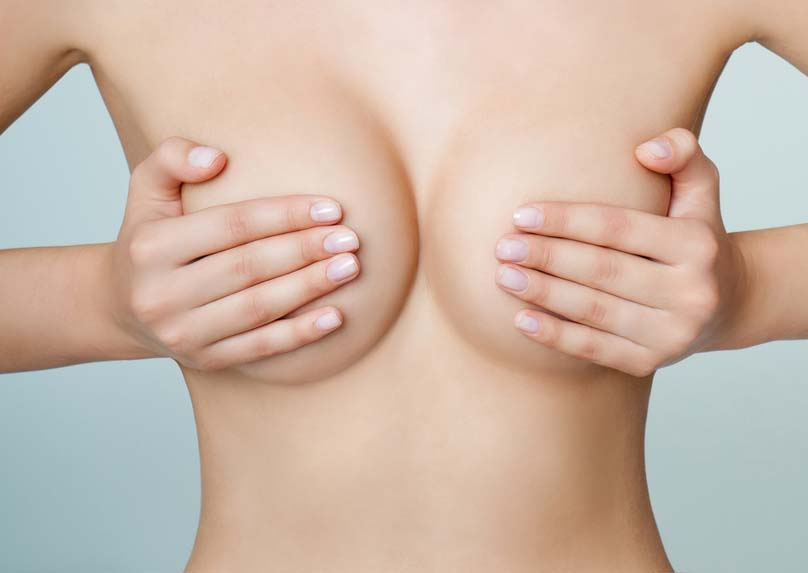 девушка держит грудь руками