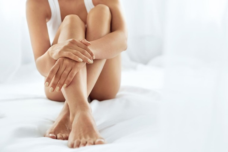 женщина сидит, сложив руки на ноги
