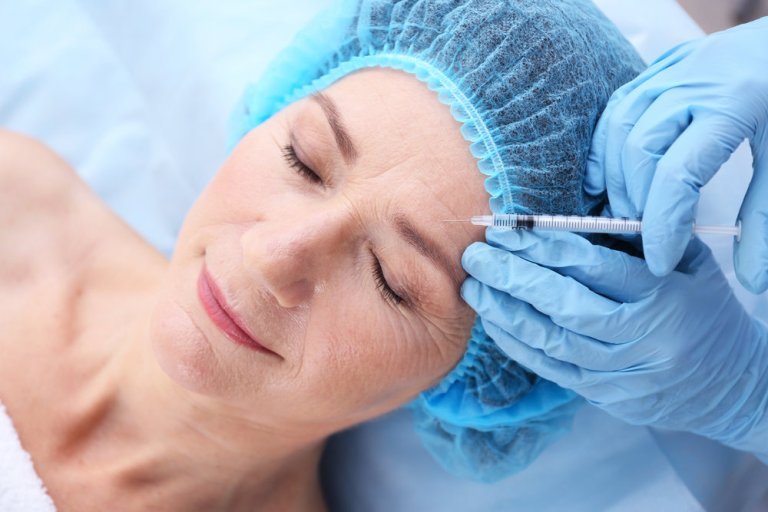 Женщине колют укол в кожу лица