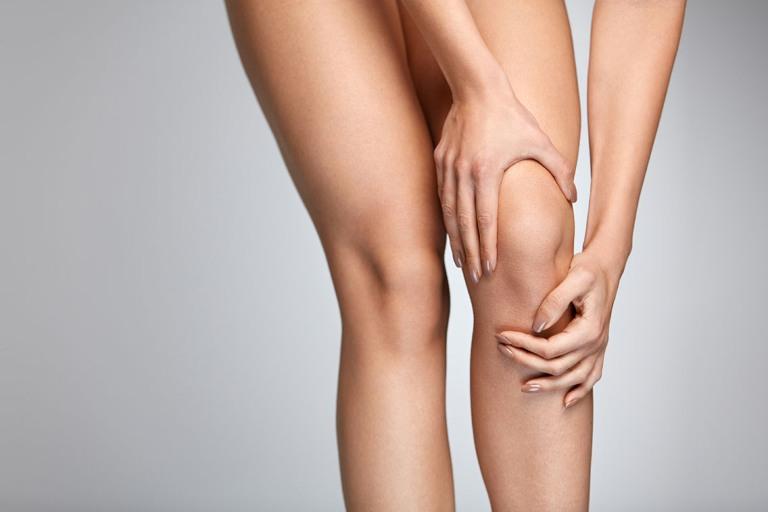 Женщина держит рукой колено