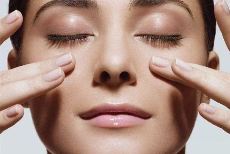 Пальцы на женском лице с закрытыми глазами
