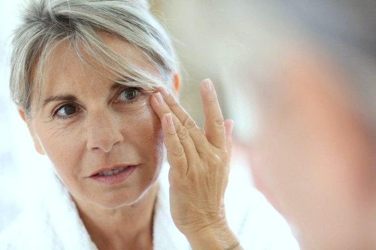 Женщина касается своего лица