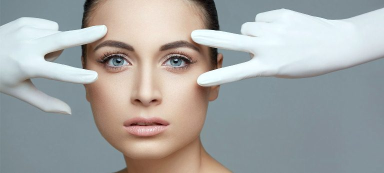 Руки врачей возле глаз