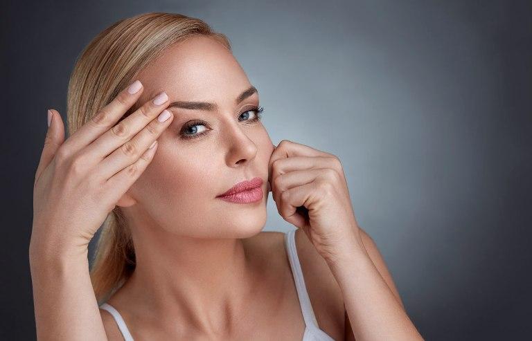 Женщина касается области брови