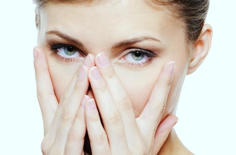 Женщина закрывает нос