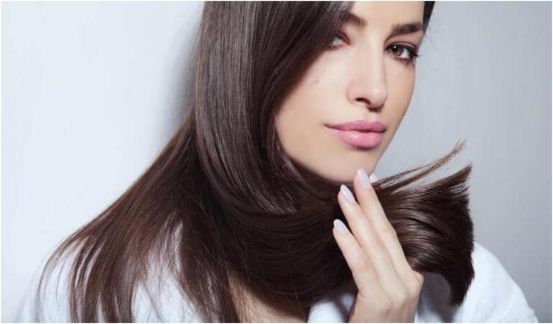 Женщина держит волосы