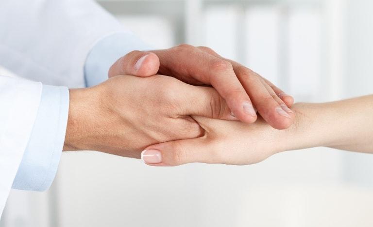 Рука пациента в руке доктора