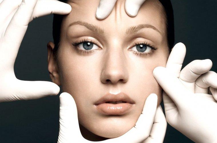Руки пластического хирурга у лица