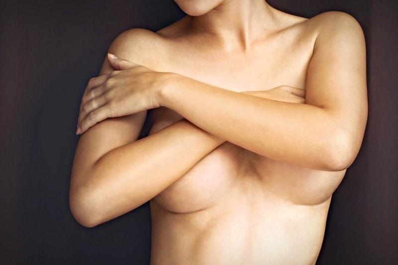 Женщина закрывает бюст