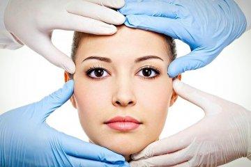 Руки хирургов возле лица