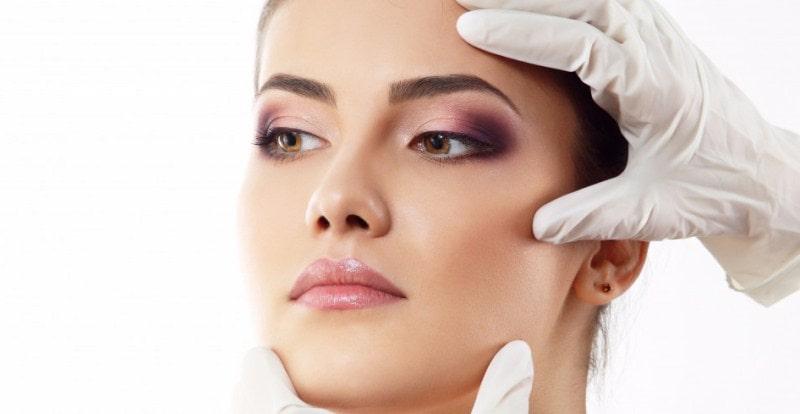 Руки хирурга на лице