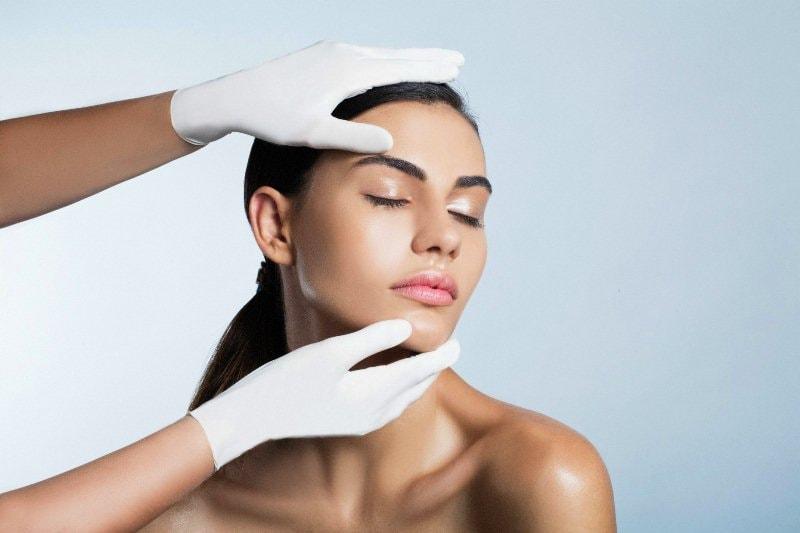 Руки пластического хирурга на лице девушки