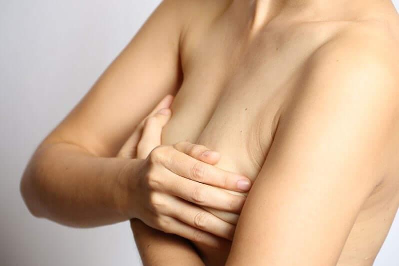 Женщина закрывает грудь руками