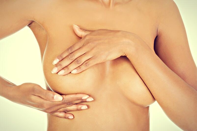 Женщина держит руками одну грудь