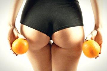 В руках апельсины возле ягодиц
