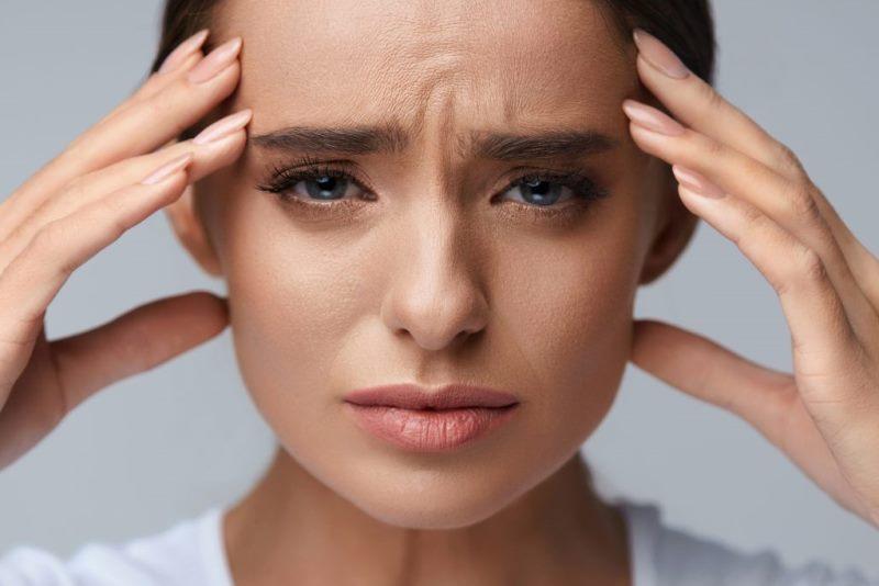Женщина грустная держится за голову