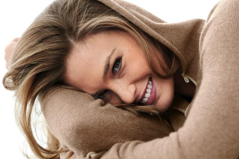 Женщина улыбается и смущается