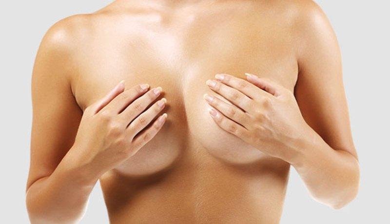Девушка закрывает грудь руками