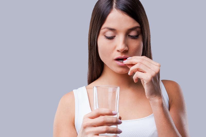 Девушка пьет витамины с гиалуроновой кислотой