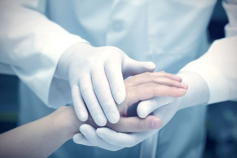 Доктор держит руку пациента