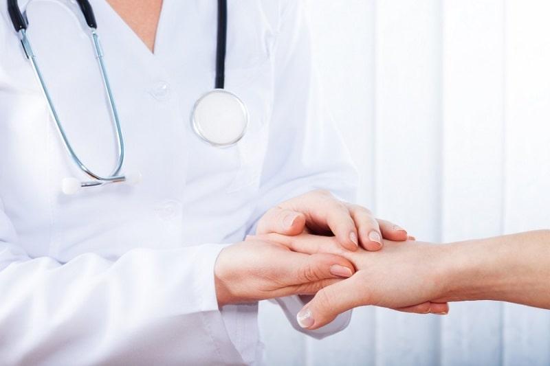 Доктор держит руки пациента