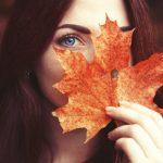 Девушка закрывает лицо красным листом