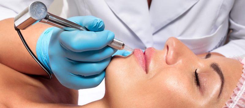 Проводится процедура перманентного макияжа губ
