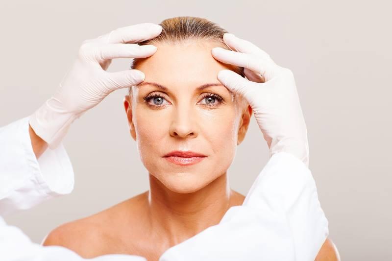 Руки хирурга возле лица женщины