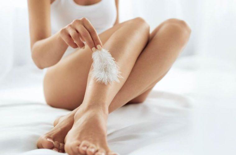 Девушка гладит ногу перышком