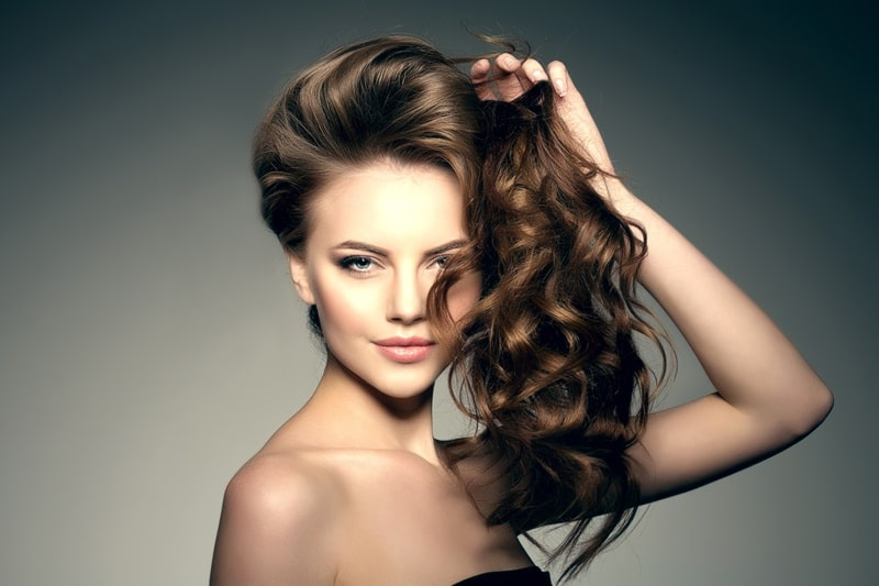 Девушка держит свои волосы