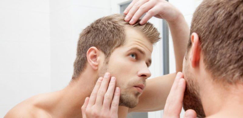 Мужчина смотрит в зеркало на волосы