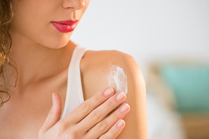 Девушка наносит крем на тело