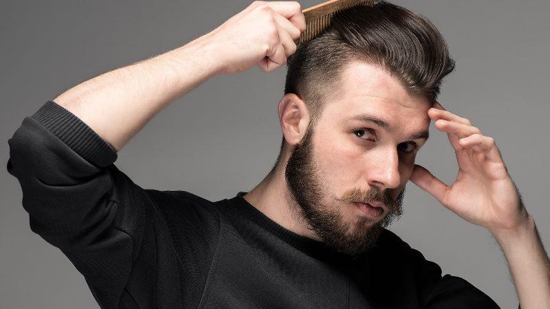 Мужчина расчесывает волосы