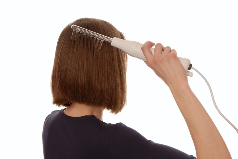 Девушка проводит дарсонвализацию волос