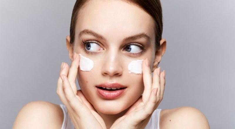 Девушка наносит крем для сухой кожи лица