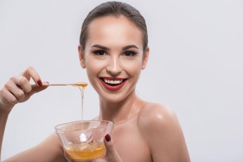 Девушка держит мед в руках