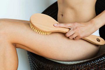 Девушка использует щетку для массажа